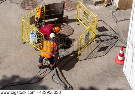 Saint Petersburg, Russia - June 08, 2021:workers Over An Open Sewer Manhole On The Street, Repairing