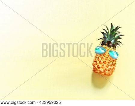 Pineapple With Blue Sunglasses On The Yellow Background.