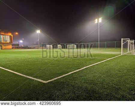 Stadium In Lights And Flashes. Empty Beautiful Football Field With Glowing Spotlights In The Evening