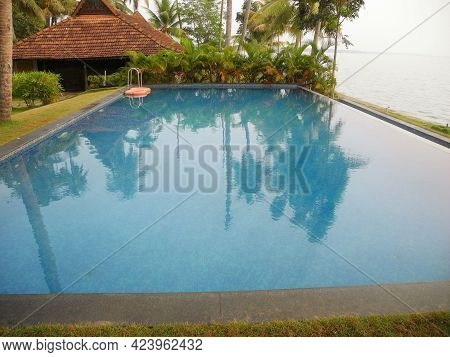 Blue Water Swimming Pool With Backwaters In Kerala. Travel Concept