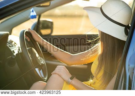 Young Driver Girl In Yellow Dress And Straw Hat Sitting Behind Steering Wheel Driving A Car. Summer