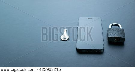 Networking Security Protection. Modern Space Grey Mobile Phone With Padlock, Key On Dark Background.