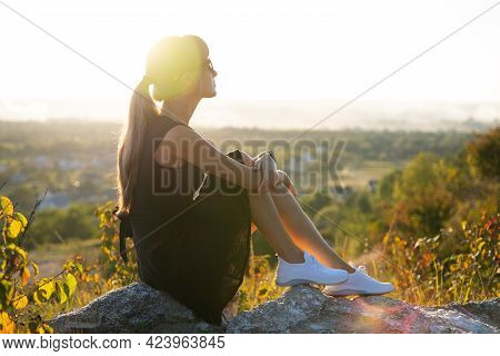 Young Pretty Woman In Black Short Summer Dress Sitting On A Rock Relaxing Outdoors At Sunset. Fashio