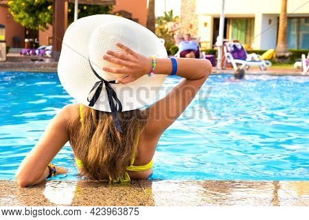 Back View Of Young Woman With Long Hair Wearing Straw Hat Relaxing In Summer In Hotel Swimming Pool