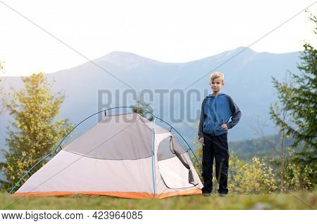 Happy Child Boy Standing Near A Tourist Tent At Mountain Campsite Enjoying View Of Beautiful Summer