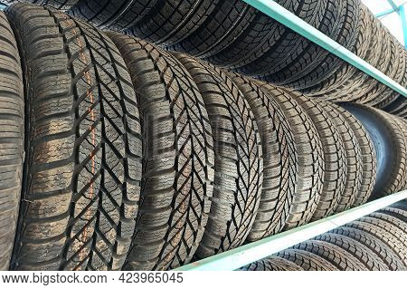 Many Black Rubber Car Tires On Store Shelf For Sale.