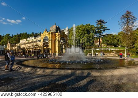 Marianske Lazne, Czech Republic - May 30 2021: View Of The Spurting Water Fountain. Yellow Colonnade