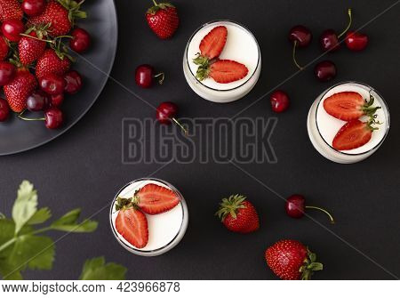 Top View Of Delicious Strawberry Panna Cotta In A Glass On Dark Background. Italian Desserts Concept