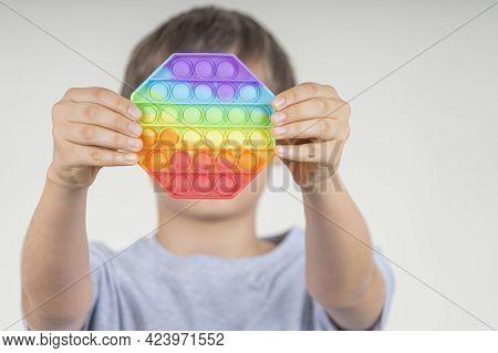 Boy Holding Sensory Pop It Fidget Toy In His Hands. Push Pop-it Fidgeting Game Helps Relieve Stress,