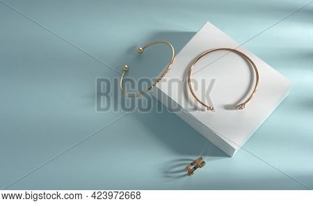 Modern Bangles And Chain Shape Ring On White And Blue Background With Copy Space