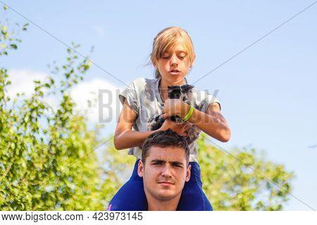 Defocused Brother Giving Sister Ride On Back. Portrait Of Happy Girl On Man Shoulders, Piggyback. Gi