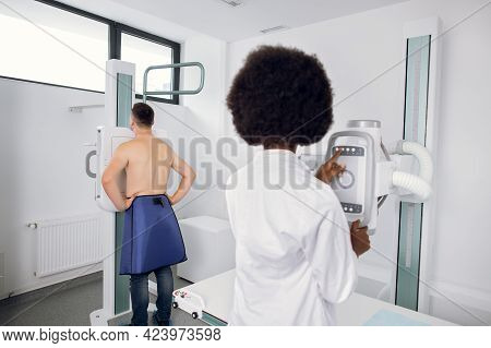 Back View Of Female Doctor Radiologist Taking Chest Scan Xray Of Young Caucasian Man In Hospital. Fl