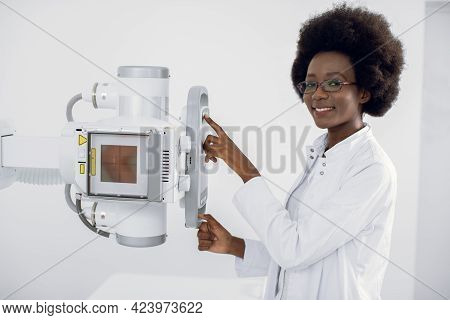 Beautiful African Woman In White Medical Coat, Standing Near The X-ray Machine In Modern Hospital Ra