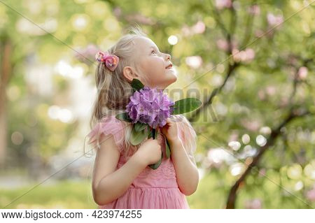 Portrait of a little girl with a rhododendron flower