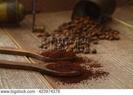 Coffee Beans And Ground Coffee In Wooden Spoons On Brown Background. With Coffee Pot And Coffee Grin