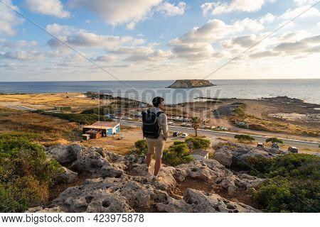 Man With Backpack Is Hiking Along A Rocky Coast At Sunset Near The Mediterranean Sea In Cyprus. Male