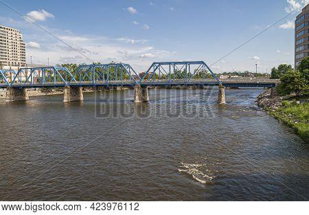 Grand Rapids, Mi, Usa - June 7, 2008: The Blue River Crosses Over Dark Brownish River Under Blue Clo