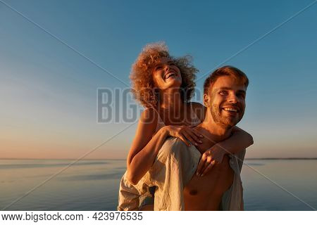Portrait Of Happy Young Caucasian Man Holding Laughing Girlfriend On His Back Near Sea. Romantic Dat