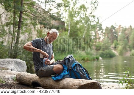 Middle Aged Caucasian Man Using Pills For Distillation Water In Bottle While Sitting On Log Near Lak