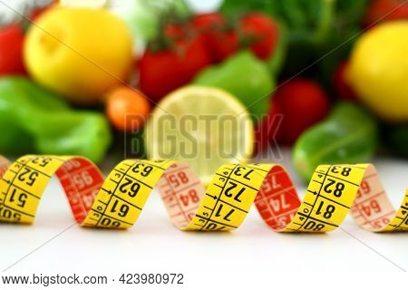 Diet Concept With Measuring Tape . Fresh Vegetables On A White Background. Tomato, Green Pepper, Car