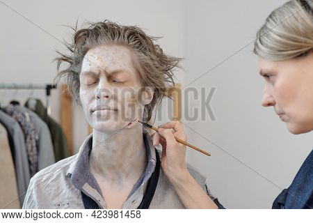 Stage makeup artist with paintbrush painting wound on face of young man
