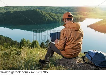 Remote Work Concept. Man Sitting Alone In Nature Wilderness Working On Laptop.