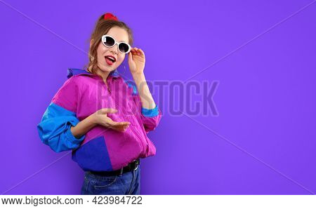 Cool teenager. Fashionable DJ girl in colorful trendy jacket and vintage retro sunglasses enjoys style of 80s - 90s vibes. Teenager Girl at disco party. Young fashion model on pink color background.