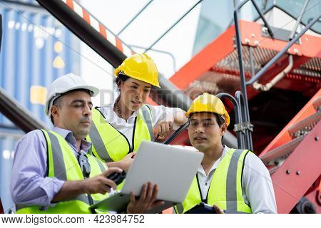 Warehouse Managers And Worker Working On Laptop In A Large Warehouse. They Work At The Heavy Industr
