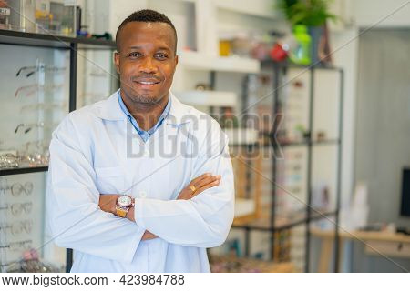 Ophthalmologist Doctor African American Standing With Arms Crossed In Optical Store. Eye Doctor, Opt