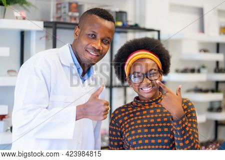 Happy Cheerful African Teenage Girl Looking For Stylish Glasses With Qualified African-american Opti