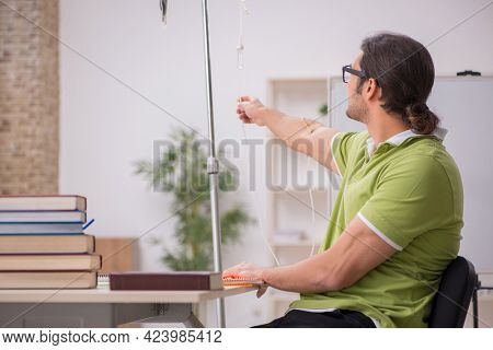 Young sick male teacher student in blood transfusion concept