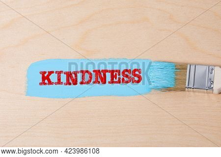 Kindness. Blue Color And A Brush On A Plywood Background