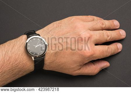 Men's Hand With A Classic Wrist Watch On A Black Background. A Fashionable And Stylish Men's Accesso