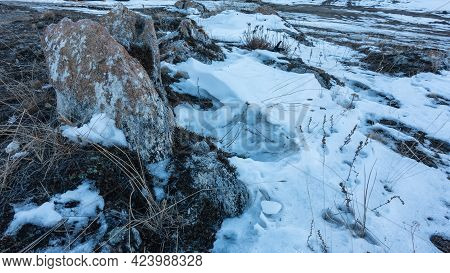 Picturesque Boulder Close Up. Brown Lichens Grow On The Gray Surface. Snow And Dry Grass On The Grou