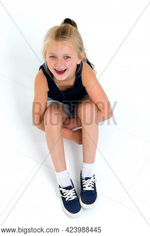 Cute Six Years Old Girl Sitting On Floor. Top View Of Cheerful Kid Looking At Camera On White Backgr