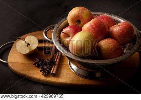 Metallic Bowl Full Of Red Ripe Apples, Scattered Cinnamon Sticks, Aniise Stars An Half Of Apple On W