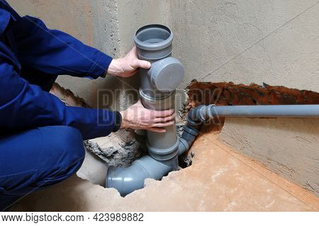 Plumber assembling pvc sewage pipes in house