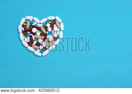 Pharmaceutical medicine pills, tablets and capsules in the shape of a heart on a blue background