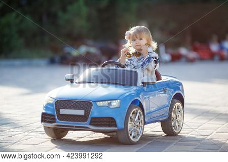 Portrait Of Cute Little Caucasian Blond Toddler Girl Enjoying The Fun While Driving A Toy Electric C