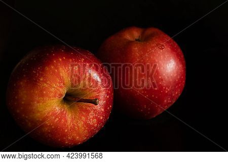 Two Ripe Fresh Red Apples With Water Drops On Glossy Peel On Black Background