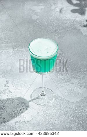Iceberg cocktail on vintage textured table. Cocktail with vodka and blue curacao liqueur. Summer day and cocktail concept. Sunshine with shadow