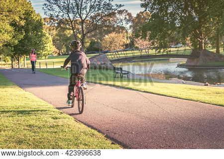 Australian Boy Riding His Bicycle Along The Bike Lane In Adelaide Park Lands On A Day