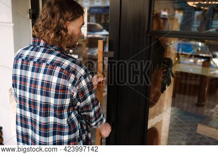 Young white cafe worker in plaid shirt opening door outdoors