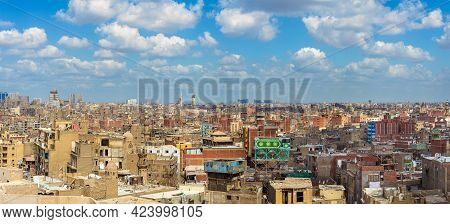 Panorama Of Shabby Buildings With Satellite Dishes On Rooftops Against Blue Cloudy Sky In Ancient Ci