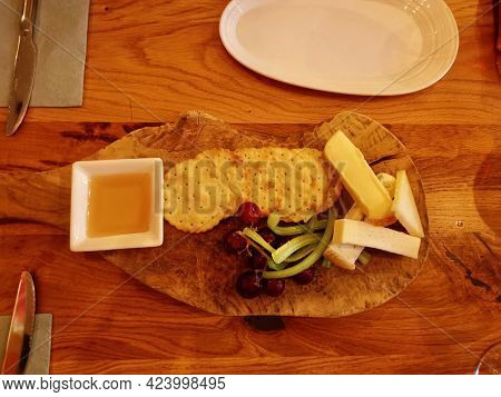 Top View Of Cheeseboard With Crackers, Celery, Honey And Grapes