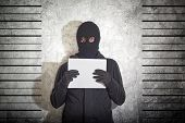 Arrested burglar concept thief with balaclava caught and arrested in front of the grunge concrete wall. poster