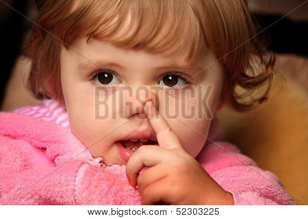 Little girl picking her nose