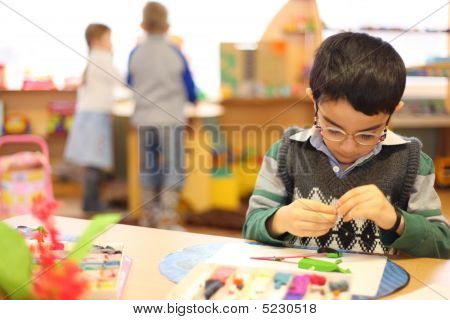Boy In Glasses Moulds From Plasticine On Table In Kindergarten
