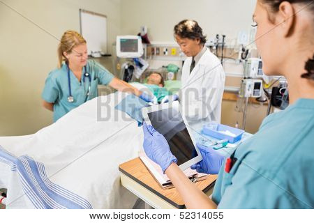 Female nurse holding digital tablet while colleague and doctor operating patient in hospital poster