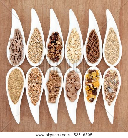 Healthy breakfast cereals in porcelain dishes over papyrus background.